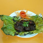 Marinated tribal chicken wrapped in banana leaves and foil, spit roasted