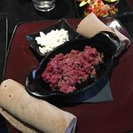raw beef with goad cheese and rolled bread (injera)