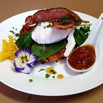 Sweet potato rosti topped with a poached egg and bacon drizzled with maple syrup