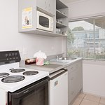 One Bedroom Holiday Apartment Kitchen with full stove, fridge, microwave, sink and plunger coffe