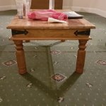 Upgrade room.Table with bent legs just by the gaps in the carpet.
