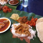 Rice on the banana leaf with fish curry, some Indian style vegetables and aplom/pappadam
