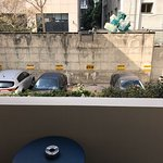 "the ""view from the balcony-room - a dirt parking with garbage containers."