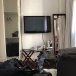 Opposite side of room - a tv with bad reception, a wardrobe with everything in