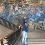 El autor con el mural de la entrada de fondo