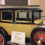 1930s car is in lobby that ties into the 1930s banking decor