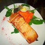 Salmón grillado sobre espinaca baby, zanahoria rallada y huevo cocido, con piel de salmón frita