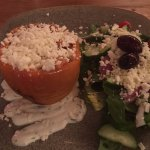 A red pepper stuffed with vegetables and rice, with feta cheese on top, Greek salad on the side