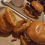 brisket bun with onion rings and chips sides