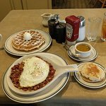 Corned beef hash with over easy eggs, pecan waffle, green chile sauce, english muffin