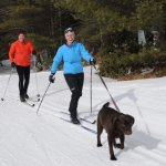 A couple and their dog enjoying the Purity Spring Resort XC & Snowshoe Reserve