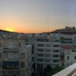 View from the Peacock Room restaurant of the sun setting beside the Acropolis