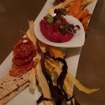 Starter at the restaurant - vegetable chips with beet hummus