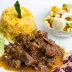 """Seco de chivo, suave y especial guiso de carne de chivo,  """"arroz achiote"""" (arroz, achiote, zanah"""