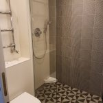 Tiled shower but no shelf, must put soap and shampoo on the floor.
