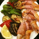 Grilled shrimps with bacon and grilled vegetables.