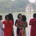 Vietnamese ladies in traditional Ao Dai east shore Hoan Kiem Lake Hanoi