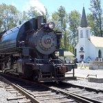 trem a vapor com a histórica igreja ao fundo