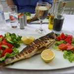 The sea bass, a glass of white wine and a bottle of water