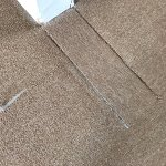 Poorly repaired carpet with staples sticking out.