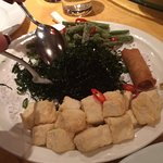 Vegetarian dish . Spring roll, seaweed, crspy asparagas with tofu squares( I think)