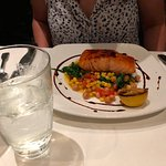 Salmon on a bed of chickpeas, corn and greens.