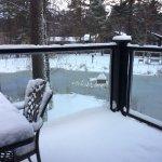 Balcony with snow overlooking lake.