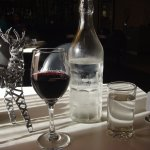 Table decoration, bottle of cold water and glass of red wine