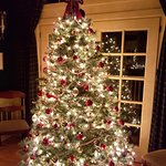 Beautifully decorated tree in front of a quiet sitting area with fireplace.