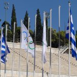 The Greece flags and the Olympic flags at the front of the stadium