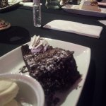 Chocolate fudge cake with ice cream. in the background citrus cheese cake.