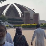 I am posing for a photo in front of the Pakistan Monument.