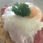 Breakfast special - crumpet topped with crispy bacon and poached egg