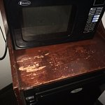scraped up cabinet where microwave sits