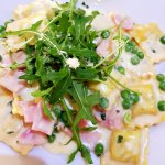 Raviolo Boscaiola Pasta filled with spinach and ricotta cheese served with peas, ham, creamy