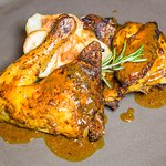 Grilled free-range cockerel marinated in herbs and spices with roast potatoes