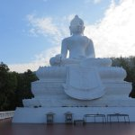 Large white Buddha statue at the top of the flight of steps