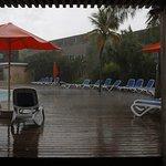 Uitzicht op het terras naast het zwembad vanaf de bar gezien (schuilend voor een tropische bui)