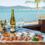 Look across the bay at Airlie Beach Town Centre while enjoying fresh seafood.
