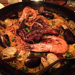 Paella, cooked to perfection, with only a few layers of rice, and crispy on the bottom.