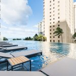 Saltwater infinity pool with water loungers overlooking Waikiki