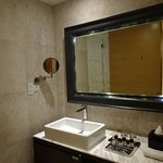 Bathroom with tub peeking out in background and note the toiletry space on the counter.