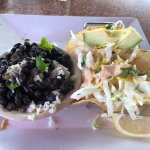 Shrimp tacos with shredded cabbage, cheddar cheese, baja sauce with black beans and rice.
