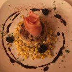 Crab cake served on bed of corn with smoked salmon.