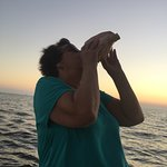 Playing the conch shell at sunset