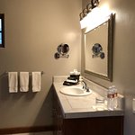 Sink with tile countertop and amenities