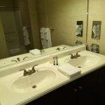 Dual bath sinks; In mirror you can see bathtub/shower.
