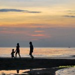 family stroll on the beach in the evening