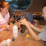 Adult visitors doing an aquifer experiment at Adult Night.