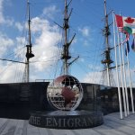 The emigrant memorial and country flags with the replica ship in the background